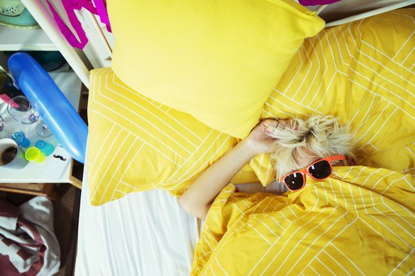 Woman wearing sunglasses in bed after party