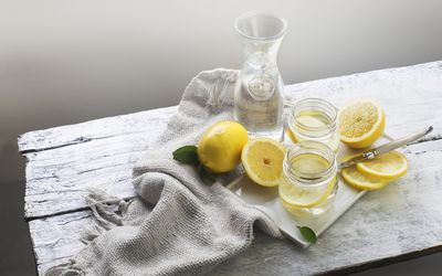On a white table, a lemon is cut into four slices. Another lemon sits, whole. There are two clear glasses with water and lemon slices, and there's a clear pitcher full of water.