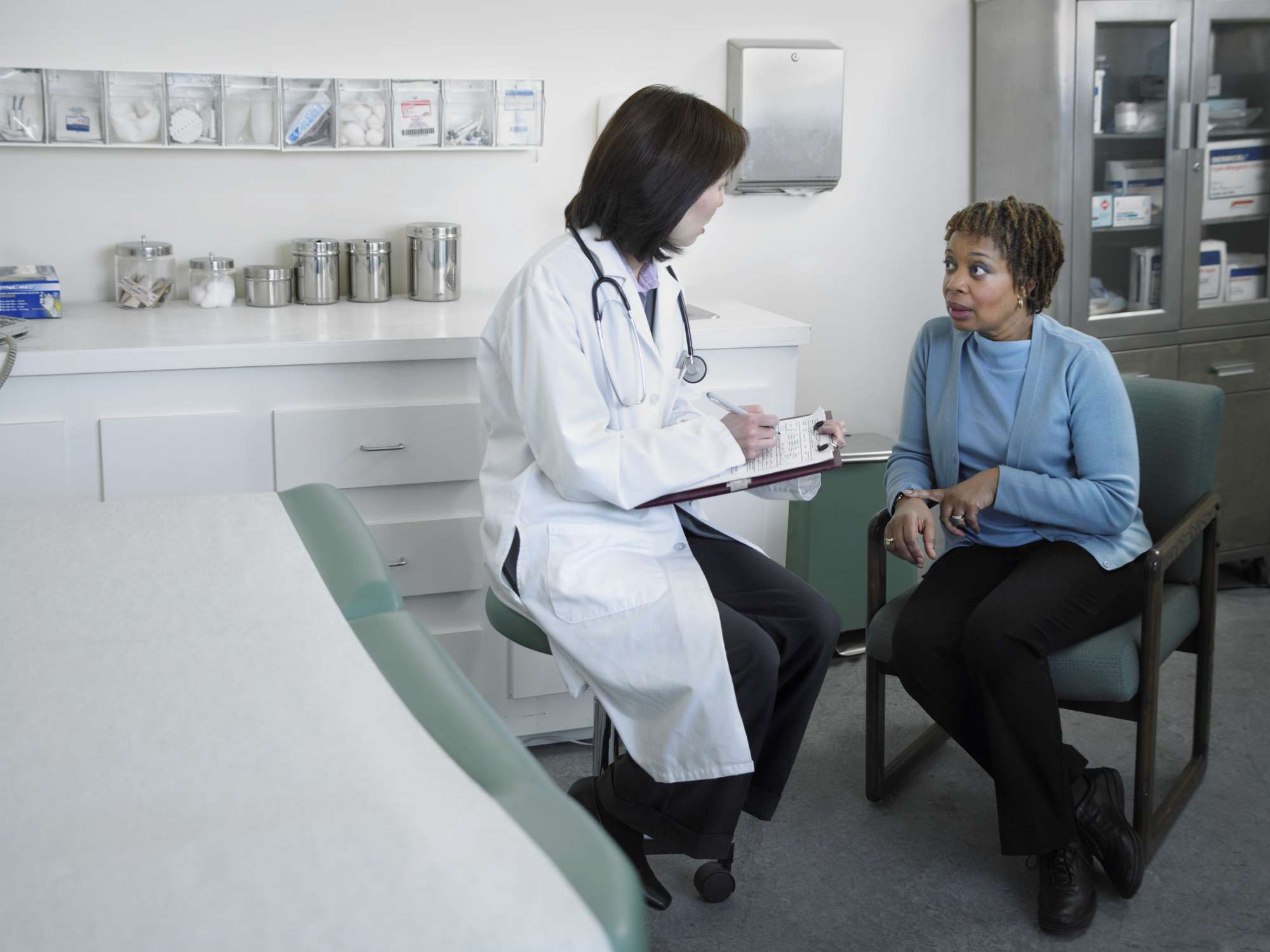 Female doctor talking to mature patient in examining room
