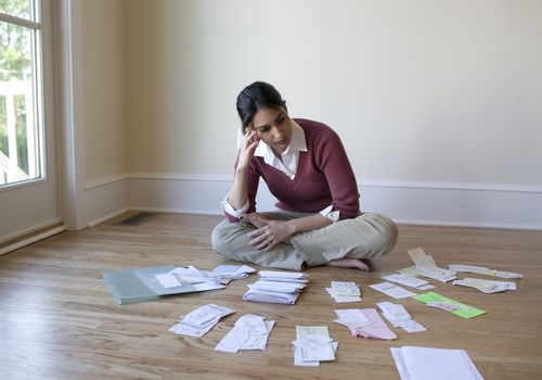 woman sitting on floor surrounded by receipts and paperwork