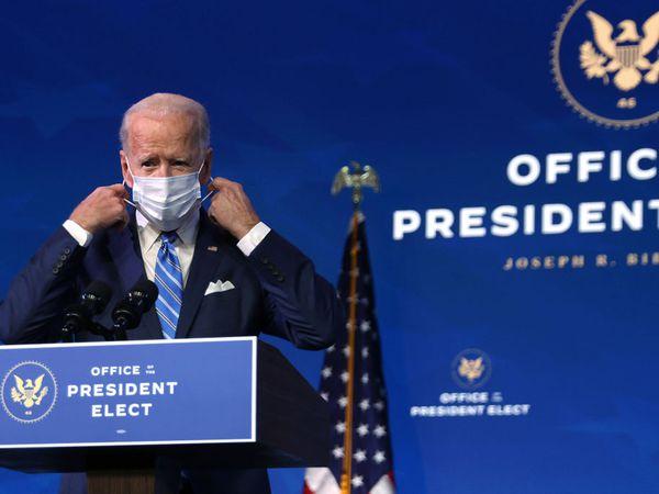Joe Biden at podium putting on mask