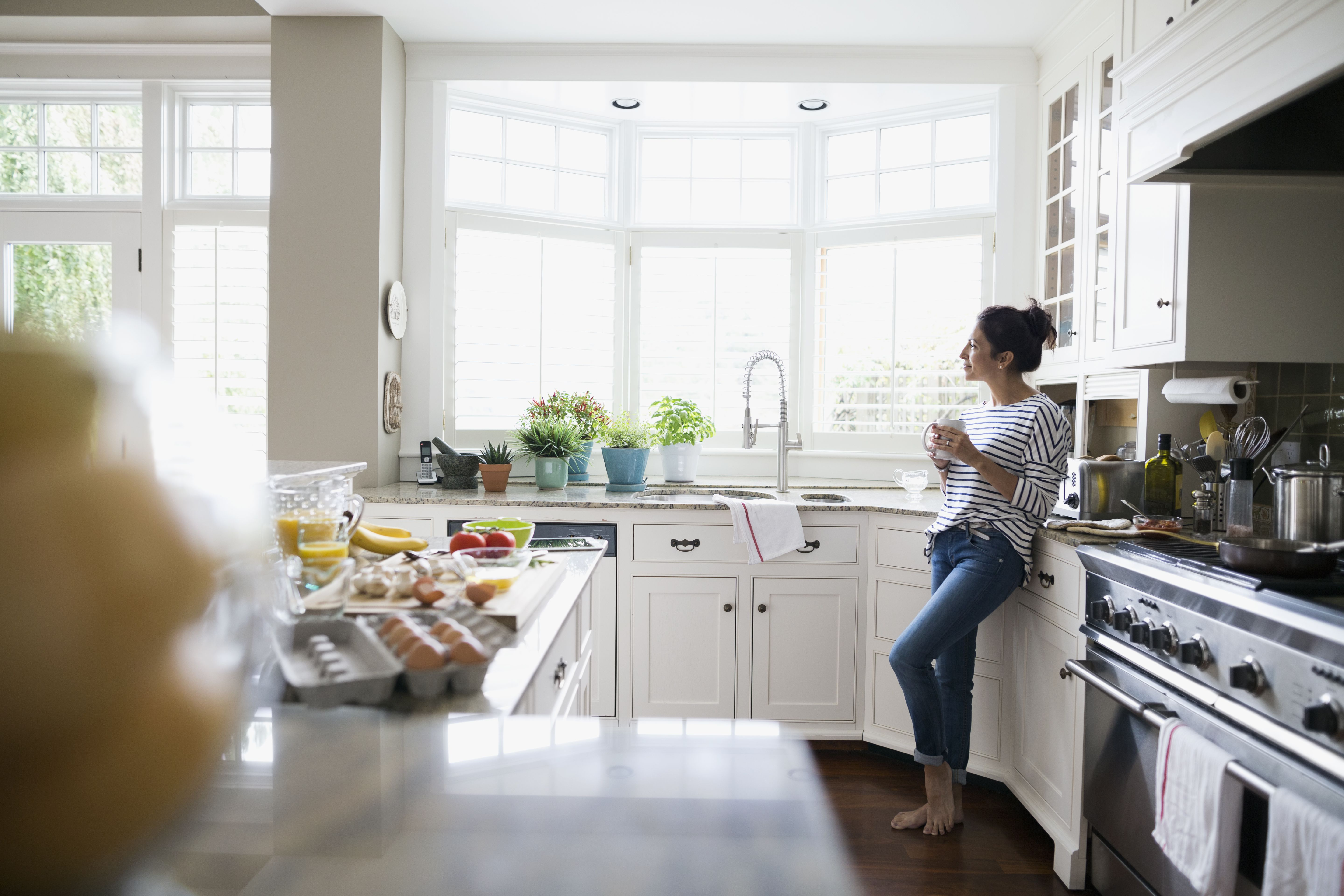 Pensive woman drinking coffee looking out window kitchen