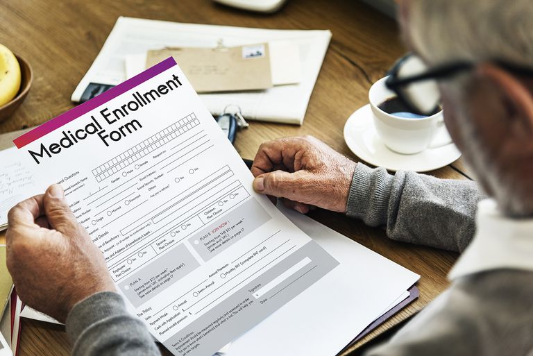 Older man holding medical enrollment form