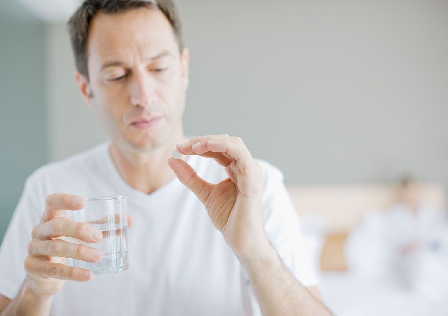 Man holding a glass of water examining a pill