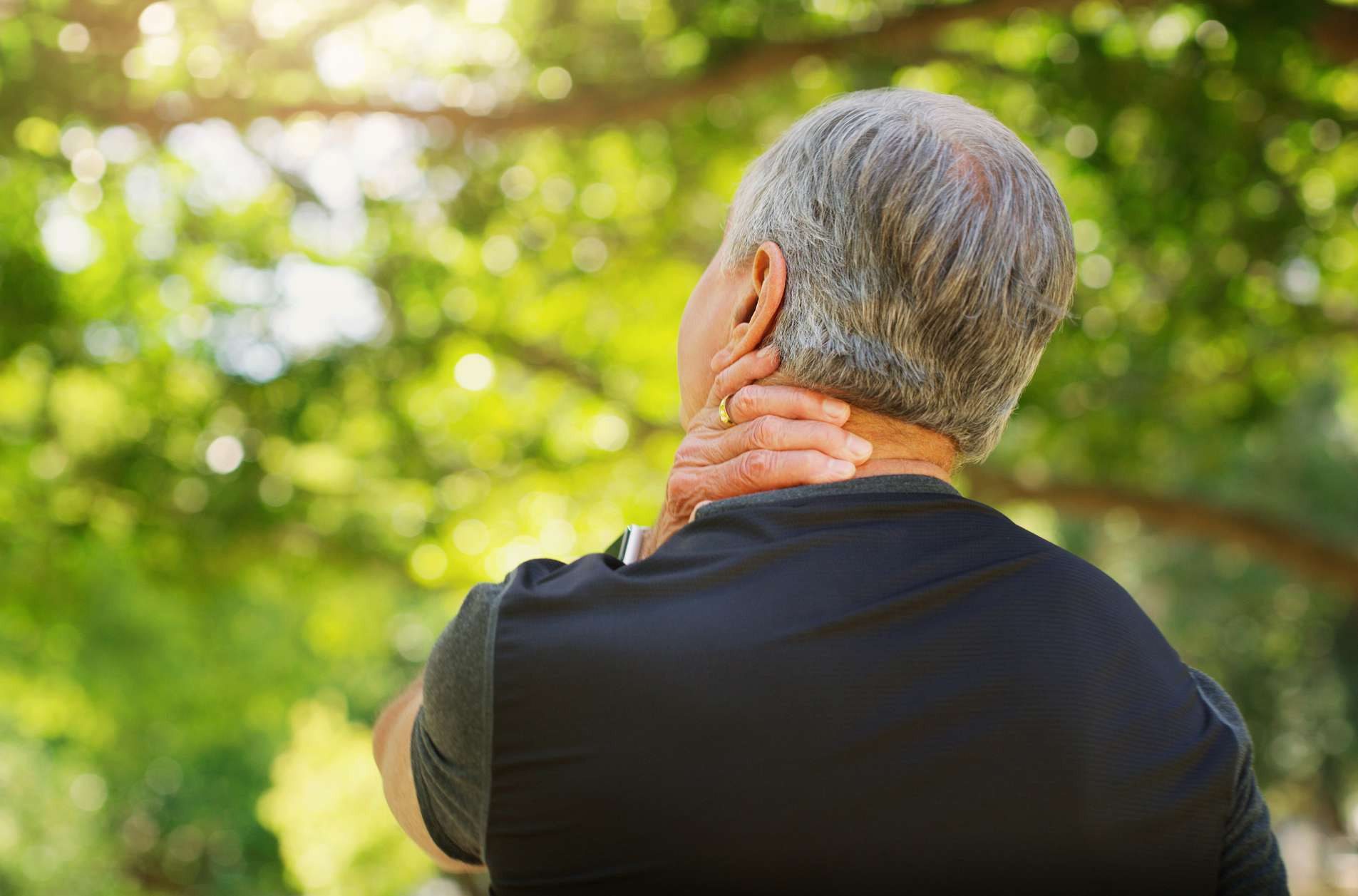 Man in park with neck pain turned away touching his neck
