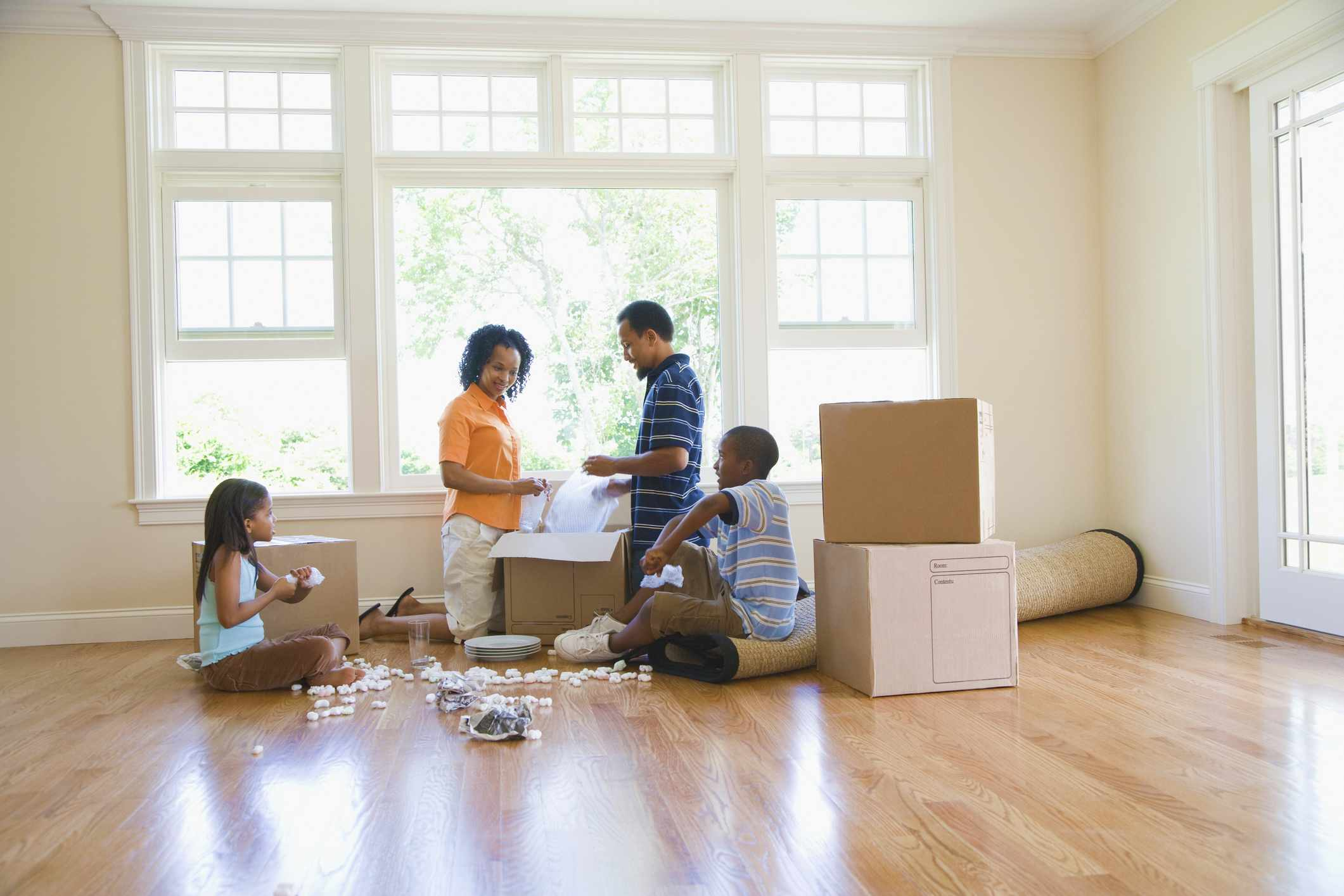 Family in an empty room with moving boxes