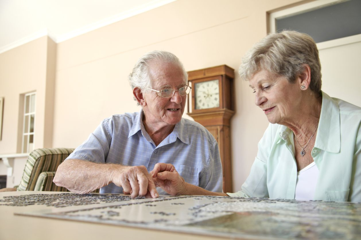 Older man and women working on a puzzle together