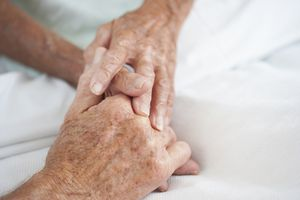 Holding hands in a hospital bed