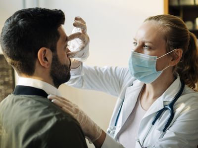 A doctor in a face mask examines a male patient's eye.