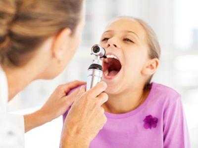 Doctor examining girls tonsils after surgery.