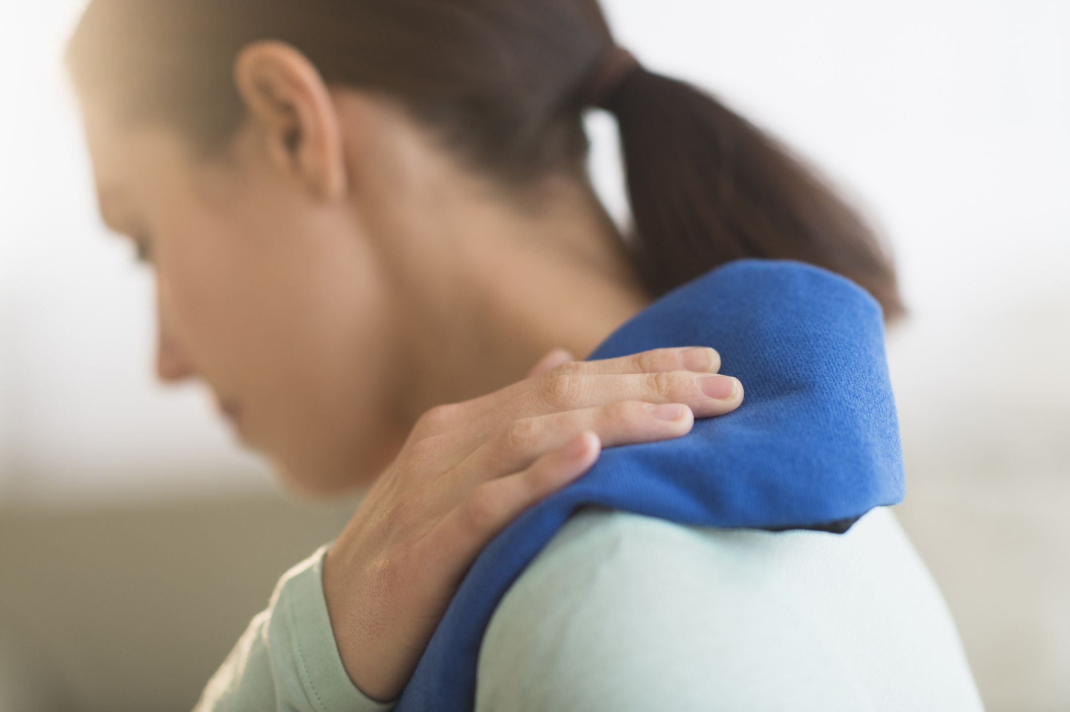 Close-up of a woman in pain holding her shoulder