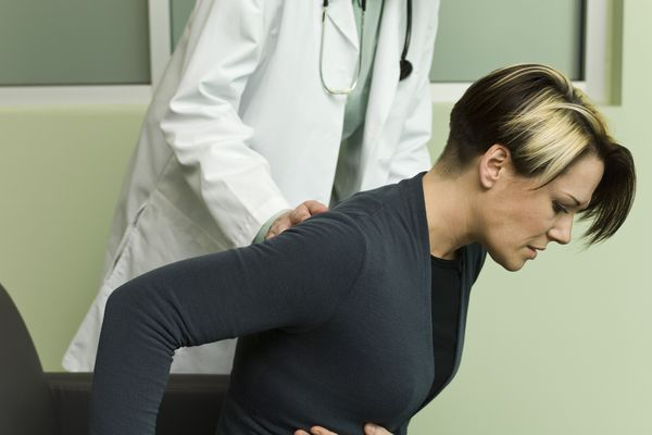 Doctor assisting patient experiencing severe abdominal pain