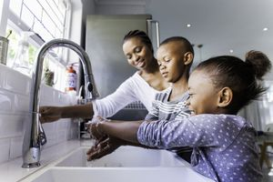 A mom teaching her kids how to wash their hands