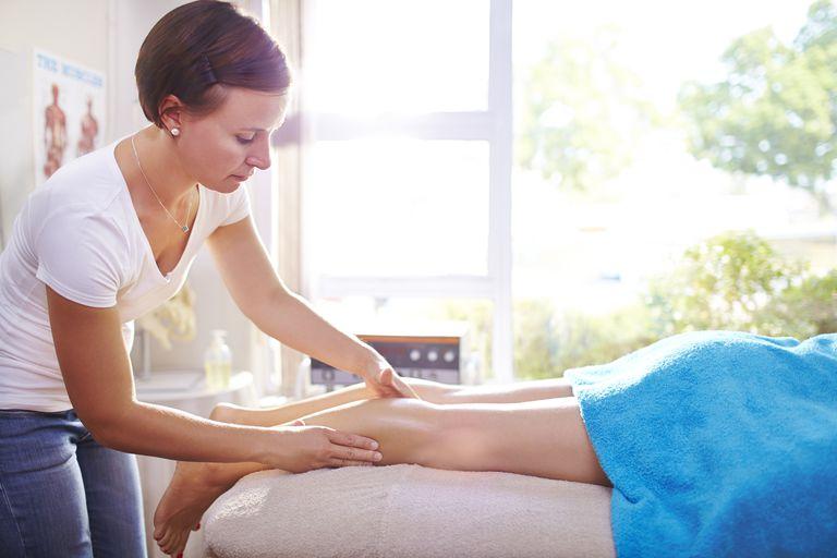 Massage therapist working on patient's legs