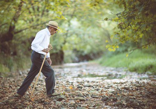 Old man walking in a creek bed