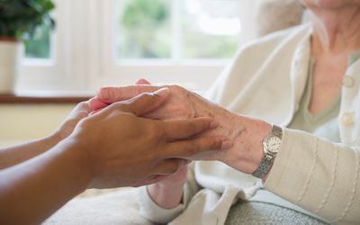 holding an elderly woman's hand
