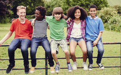 Group of pre-teens sitting on a fence.