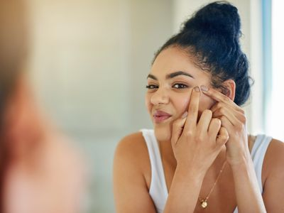 woman looking at acne in mirror