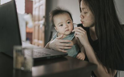 asian chinese mother checking her baby boy son body temperature using thermometer while consulting her pediatrician doctor online using laptop