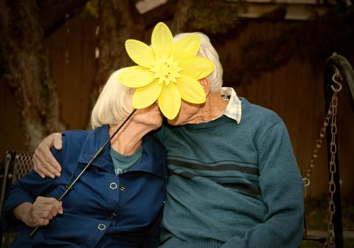 Older couple kissing being a fake flower