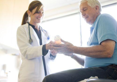 Doctor giving prescription bottle to senior patient