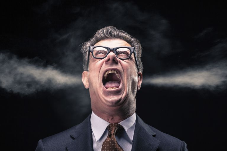 An angry man in a suit and glasses yelling with steam coming out of his ears