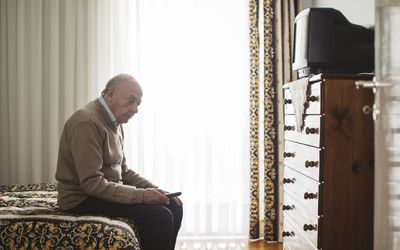An older man sitting on the edge of his bed