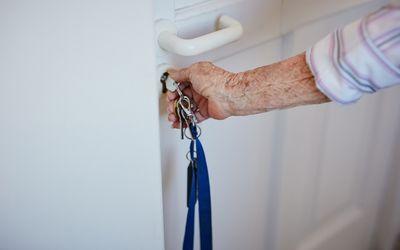 Older hand with key in a door