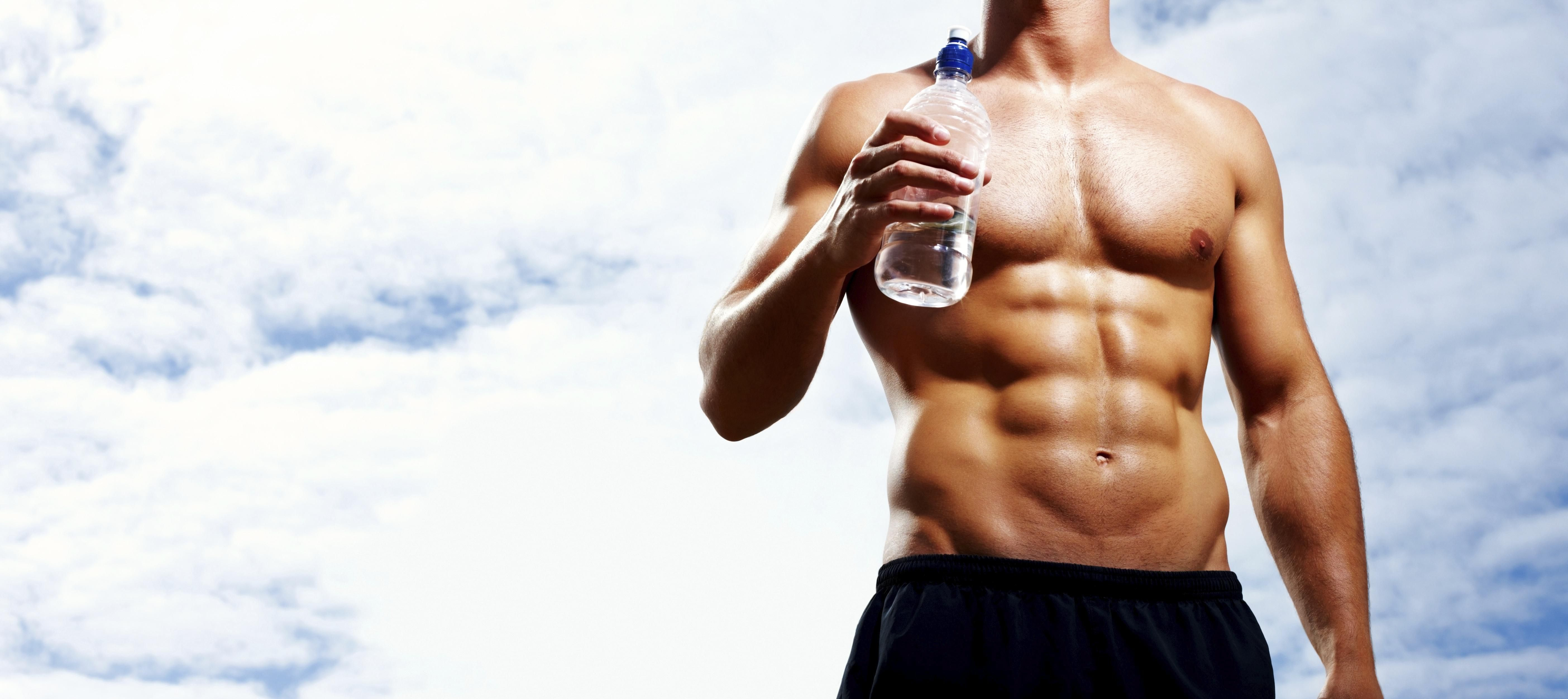 Mid section of muscular man with bottle aganist cloudy sky
