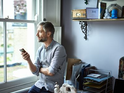 Mature businessman using phone in home office looking through window