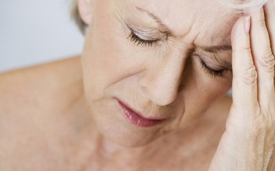 senior woman holding temple in pain