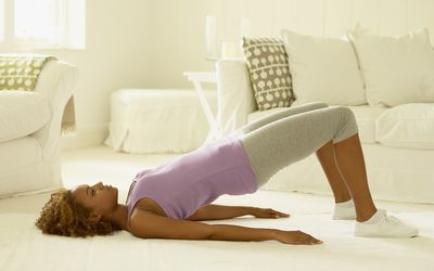 a woman performing back bridge stretching exercise