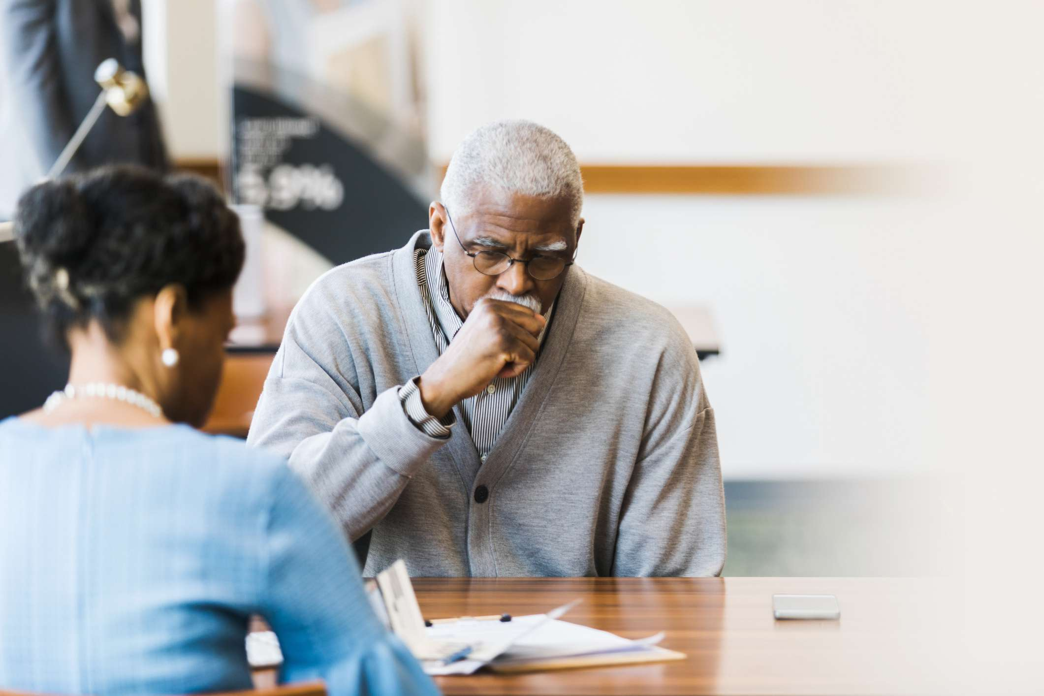 Senior African American man talks with female loan officer about obtaining a loan.