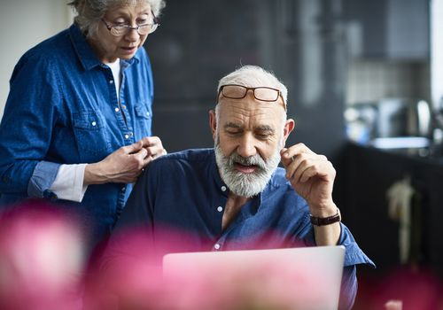 Senior man and woman looking at laptop screen