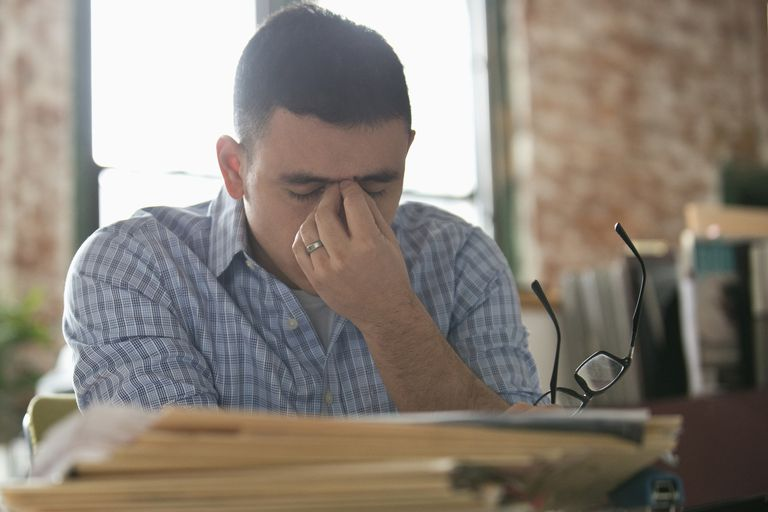 Anxious Hispanic businessman rubbing forehead at office desk