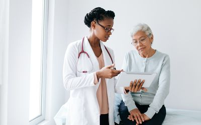 A Black, female physician uses a tablet to explain something to an older patient.