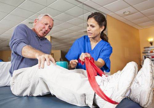 Man with knee pain working with a physical therapist