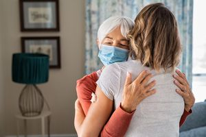 An older adult woman wearing a face mask hugging a younger blonde woman.