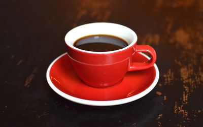 Black coffee in a red cup and saucer.