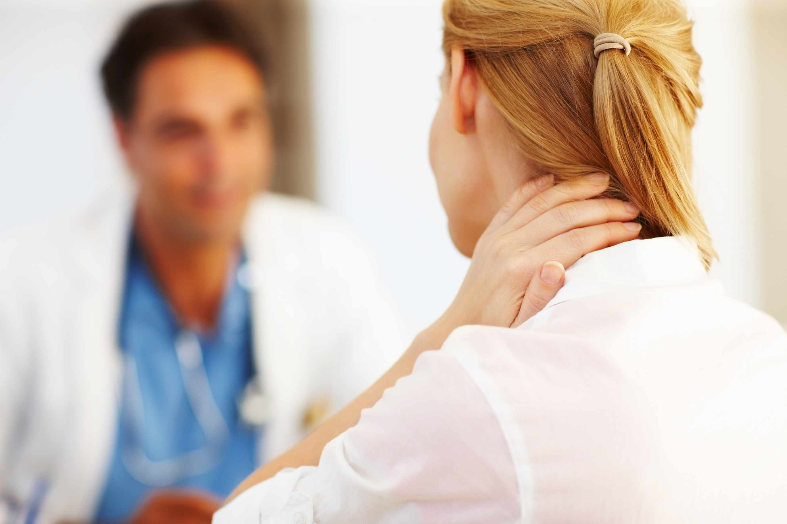 Woman talking to her doctor holding the back of her neck in pain