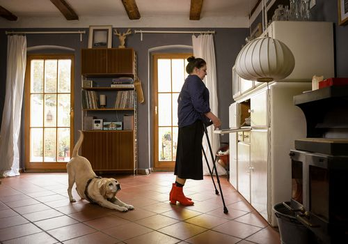 Woman on crutches in kitchen
