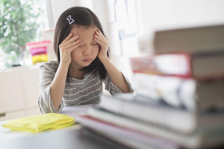 Anxious student rubbing forehead doing homework