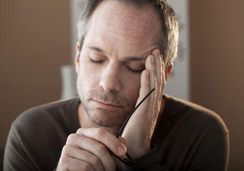 Man rubbing head at home