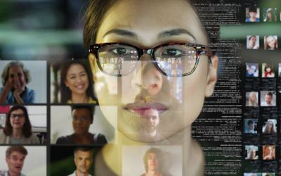 A woman with glasses reflected in a computer screen with many Zoom meetings/video conferences open.