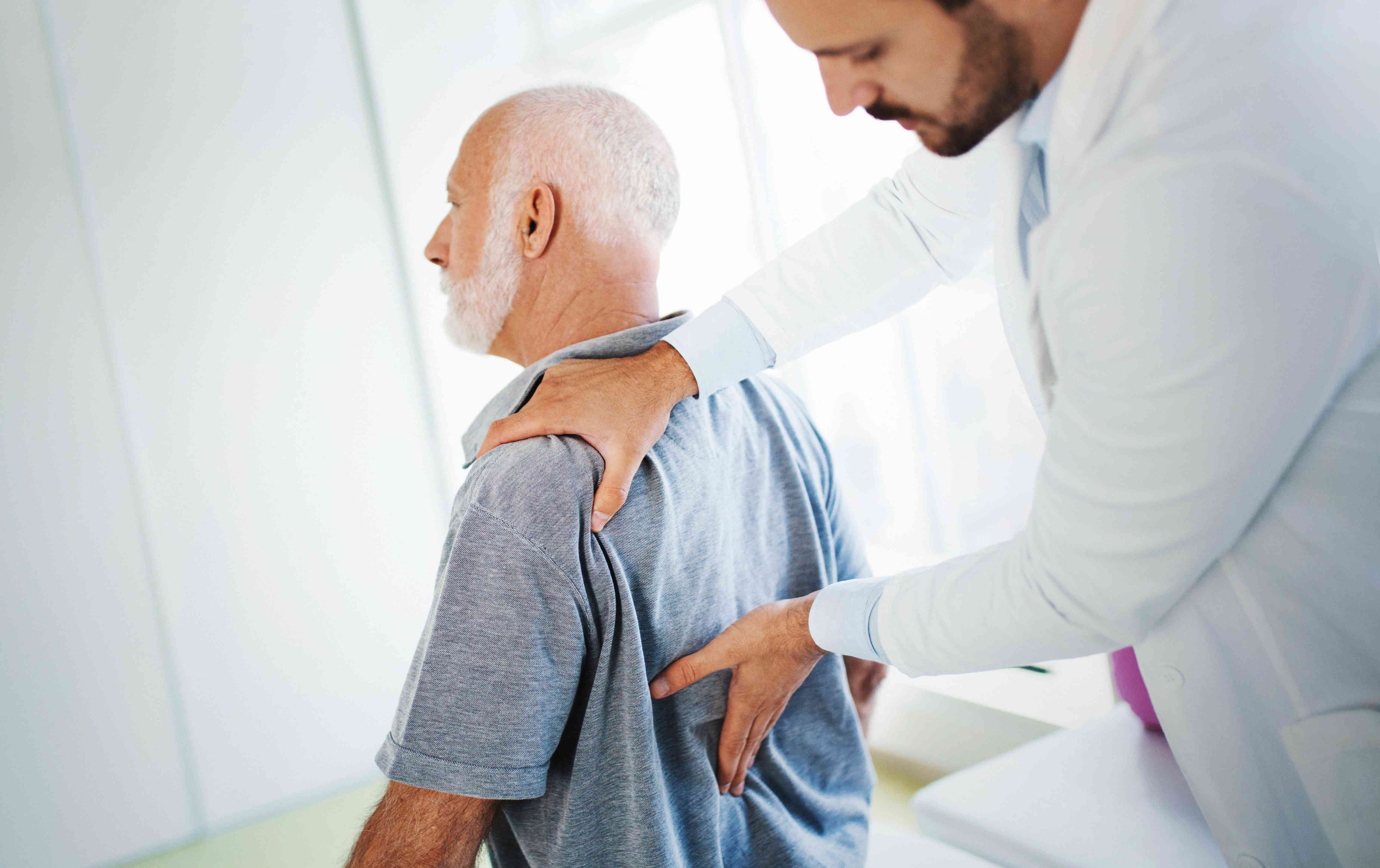 Doctor examining man with lower back pain
