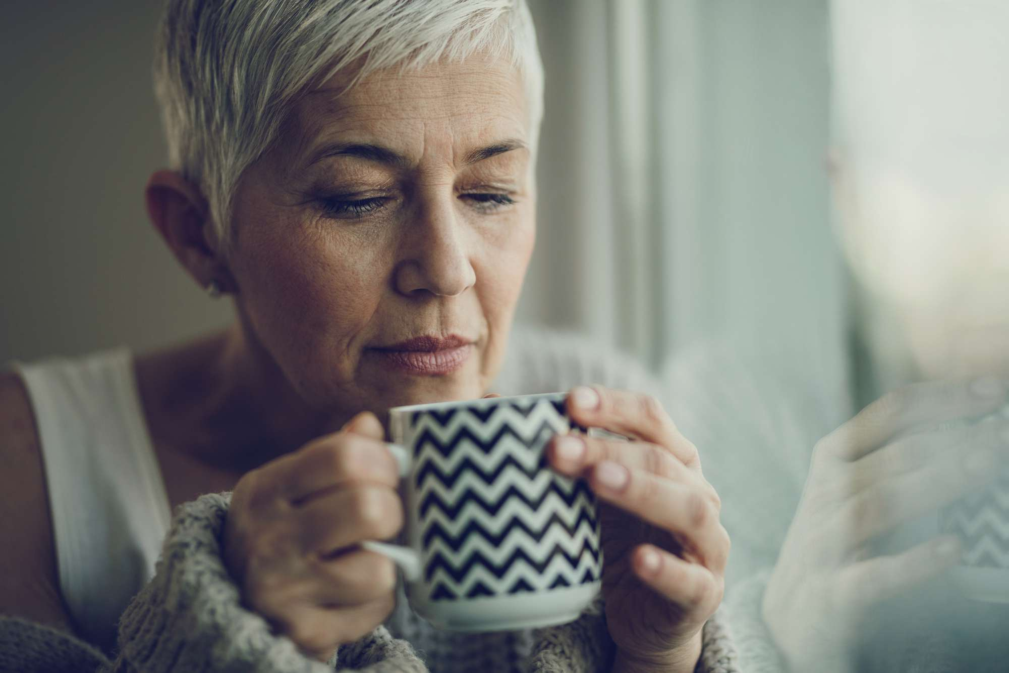 An older woman smelling coffee