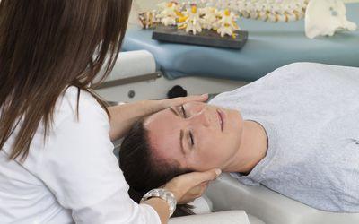 Chiropractor adjusting neck of patient