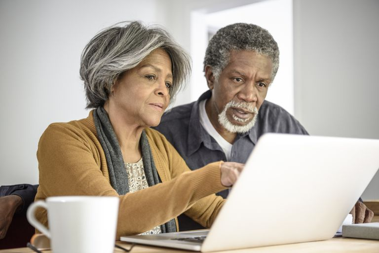 elderly couple looking at computer screen together