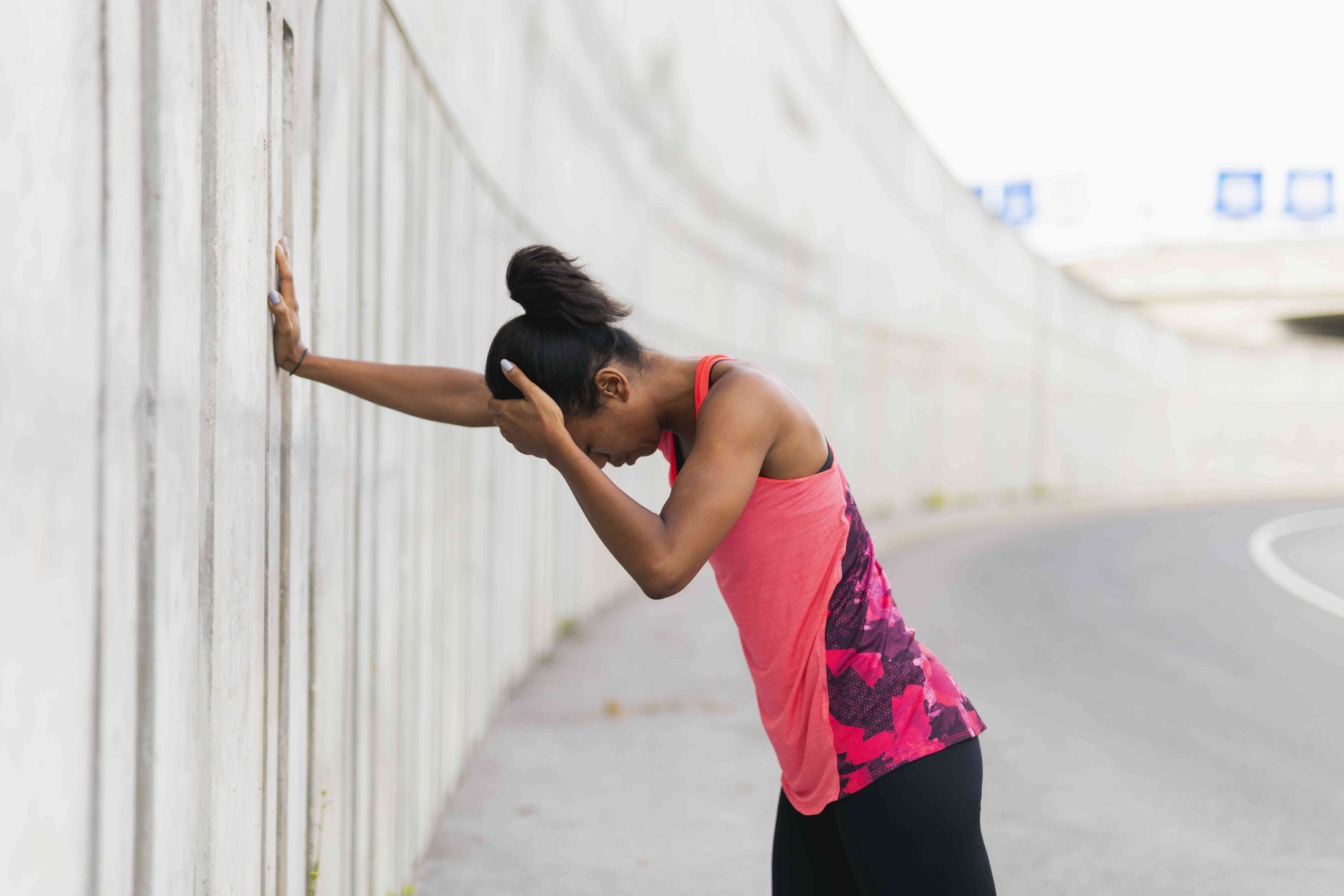 A tired jogger leaning against a wall