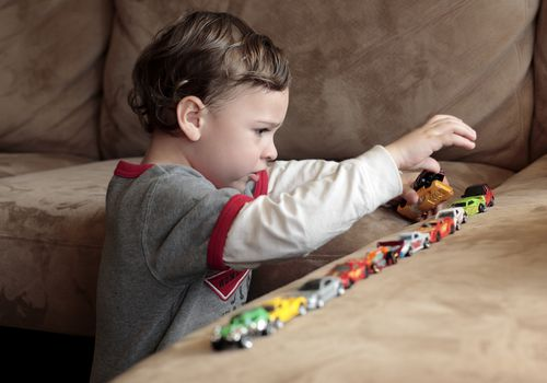 a young boy playing with toy cars